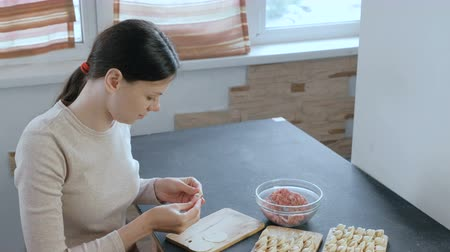 pelmeni : Woman makes dumplings with mince meat, looks at camera and smiles.