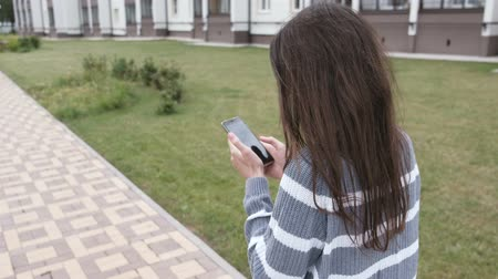 mock : Unrecognizable brunette woman types a message on mobile phone walking near the home. Back view. Stock Footage