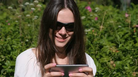 pálido : Woman is playing a game on mobile phone sitting in park in sunny day. Vídeos