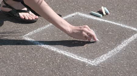 özel öğretmen : Woman draws a hopscotch on the asphalt with white chalk. Close-up hands.