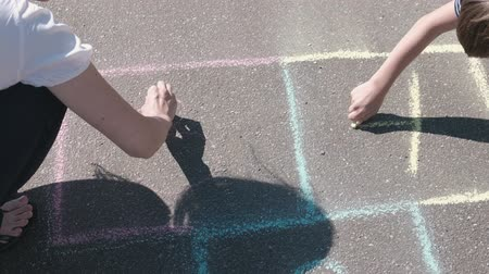 Mother and son draw numbers two and three on the hopscotch on asphalt.