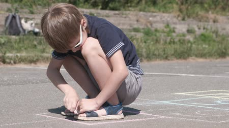 schoolyard : Boy is drawing hopscotch on the asphalt. Close-up view.