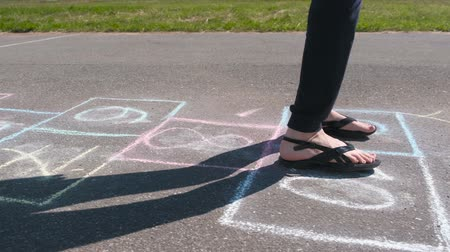 sandals : Girl teenager jumps playing hopscotch in the street. Close-up legs. Side view. Stock Footage