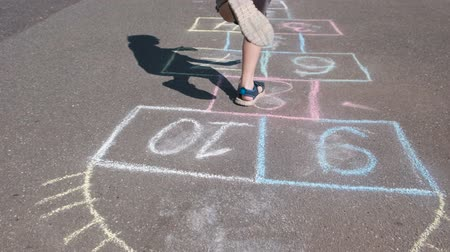 driveway : Boy jumps playing hopscotch in the street. Close-up legs.
