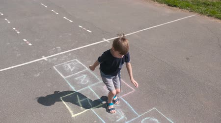 Boy jumps playing hopscotch in the street. Front view.