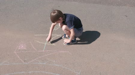 Boy draws a ship with blue chalk on the asphalt. Close-up hands. Wideo