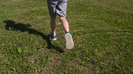 Boy runs fast on the green grass, close-up legs in sandals. Wideo