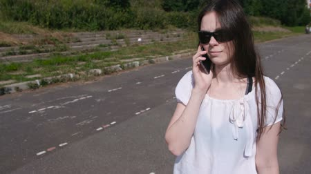 Young brunette girl walking in the stadium, dials a number on mobile phone and waiting for an answer. Wideo