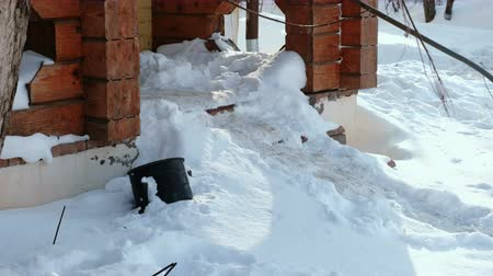 Steps of stairs covered with snow. Close-up entrance to the cottage in winter.