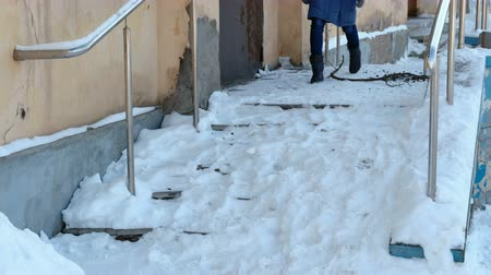 Slippery stairs. Unrecognizable woman in a blue down jacket walking down a snowy staircase.