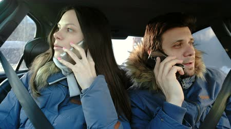 Happy man and woman speaking their cellphones and sitting in car. Front view.