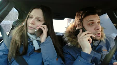 Man and woman swearing their cellphones and hysterical laughing sitting in car.