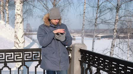 Man in blue down jacket with fur hood using his cellphone for web in a winter Park. Стоковые видеозаписи