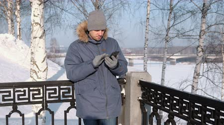 Man in blue jacket with fur hood wipes the phone screen with his hand in gloves in a winter Park. Стоковые видеозаписи