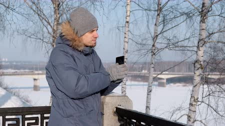 Man in blue down jacket with fur hood removes a glove using his cellphone for web in winter Park.