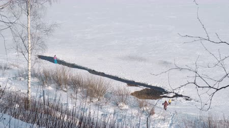 People walk along the banks of a frozen river in the winter Park.