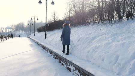 Young woman in blue down jacket walks along the border in winter Park and look at the sky, back view