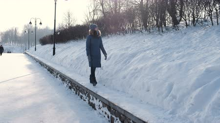 Young woman in blue down jacket walks along the border in winter Park and look at sky, front view.