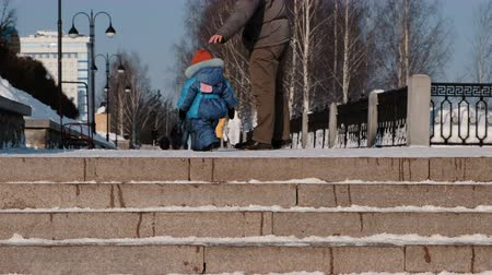 Unrecognizable child walks in winter Park with his father next to snowy staircase. Стоковые видеозаписи
