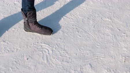 Close-up of the womans feet in boots draw patterns in the snow