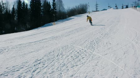 Man in yellow jacket goes down the mountain on a snowboard slope next to the lift. Side view Стоковые видеозаписи