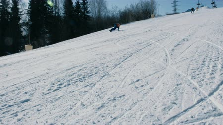 Teenage boy of 12 years in blue suit sliding on a snowboard from snow descent next sky lift and falls. Vídeos