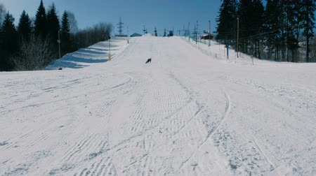 Teenage boy of 12 years in blue suit sliding on a snowboard from snow descent next sky lift. View from afar. Стоковые видеозаписи