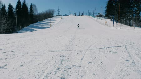 Teenage boy of 12 years in grey suit sliding on a snowboard from snow descent next sky lift. View from afar. 動画素材