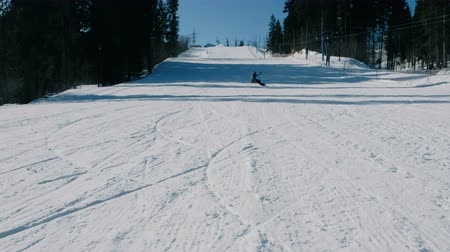 Teenage boy of 12 years in grey suit sliding on a snowboard from snow descent next sky lift. Front view.