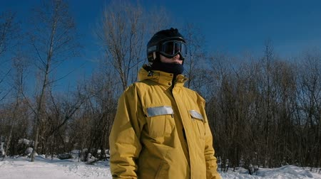 Closeup man in yellow jacket sliding snowboarder look around in winter city park. Stok Video