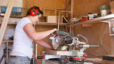 earmuffs : Woman sawing a wood board with a circular saw.