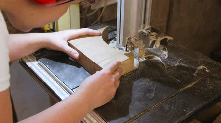 Craftswoman is cutting a wood workpiece from wood with bandsaw.