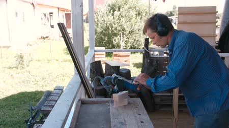 Carpenter polishes a wooden parts on a grinding machine.