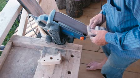 Carpenter polishes a wooden parts on a grinding machine. Close-up hands.