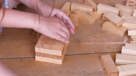 Little girl builds a tower from wooden blocks. Close-up hands. Stok Video