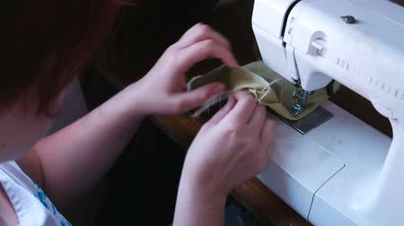 Woman sews on a sewing machine. Hands close-up.
