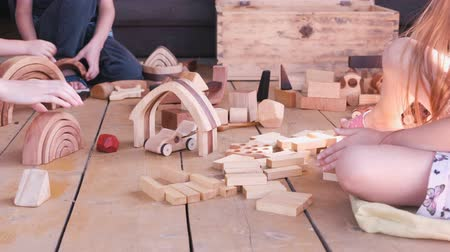 Children are playing with wooden toys. Close-up hands.
