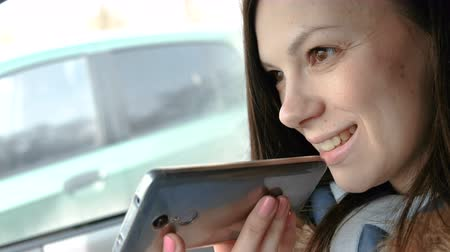 Young beautiful woman speak a voice message on a mobile phone sitting in the car and smiles.