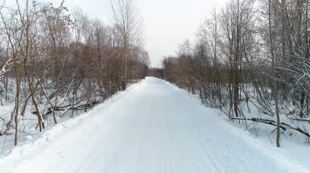 Winter road in the snow, aerial footage. Camera move ahead.
