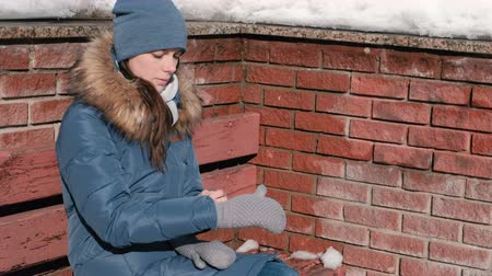 Woman chilly. She puts on mittens sitting on the bench. Brick wall in background. Стоковые видеозаписи
