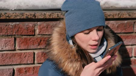 Woman is speaking audio message on mobile phone sitting in winter park. Closeup face front view.