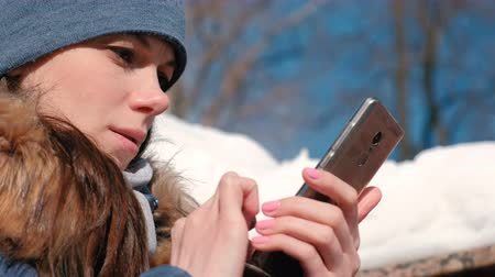Woman is browsing internet pages on mobile phone sitting in winter park. Closeup face. Stok Video