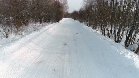 Winter road covered with snow, aerial footage. Camera move backward slowly.