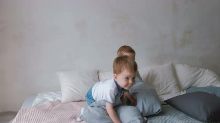 Twin boys toddlers are lying on the bed, throwing pillows, jumping and laughing.