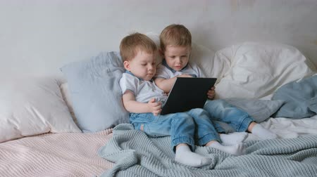 Kids with tablet. Two boys twins toddlers looking cartoon at tablet lying on the bed. Stok Video