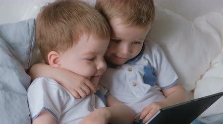 Kids with tablet. Two boys twins toddlers looking cartoon at tablet lying on the bed. Vídeos
