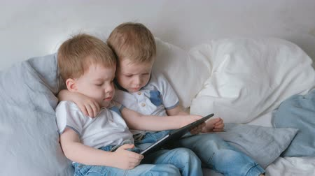 Kids with tablet. Two boys twins toddlers looking cartoon at tablet lying on the bed. Стоковые видеозаписи
