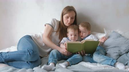 Family mom and two twin brothers toddlers read books laying on the bed. Family reading time.
