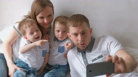 Dad makes family selfie on mobile phone. Mom, dad and two brother twins toddlers.
