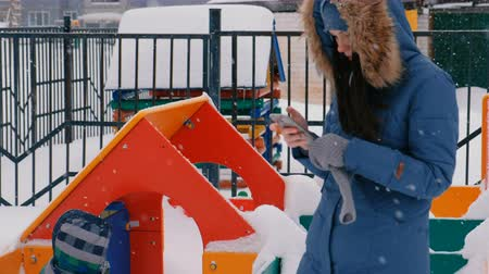 Mom calls on a mobile phone while her son walks on the playground in the winter during snowfall. Wideo
